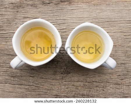 Two white teacup with tea on wood - stock photo