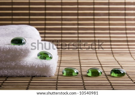 two white towels and five glass green stones - stock photo