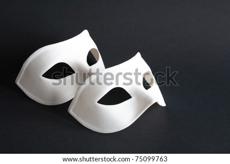 Two white venetian masks on black background