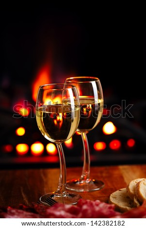 two white wine glasses  with cozy fireplace  background - stock photo