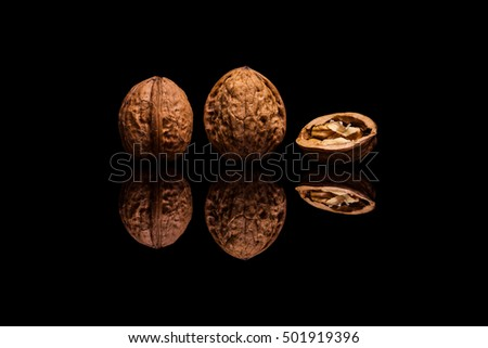 Two whole and one halved walnuts isolated on black reflective background