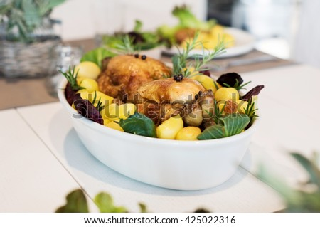 Two whole grilled chickens with herbs, rosemary and baked potatoes served in a pan on table. Closeup of roasted chickens made by chef in a restaurant. Healthy meal served for lunch.  - stock photo