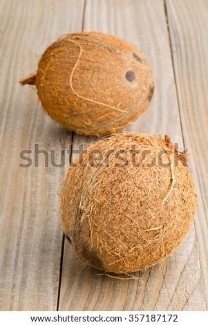 Two whole uncut coconuts on wooden table background - stock photo