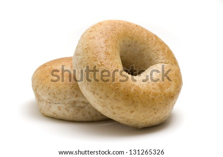 Two whole wheat bagels isolated on white background. - stock photo