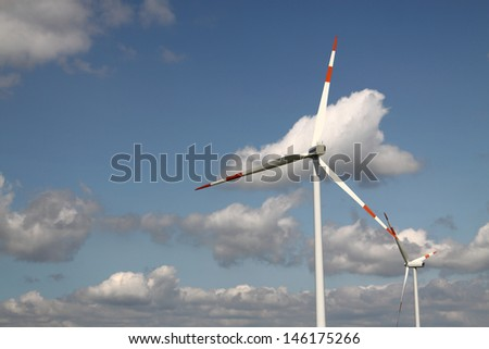 Two wind generators with blue sky and clouds