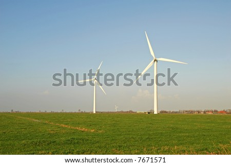 Two wind turbines on a meadow with blue sky - stock photo