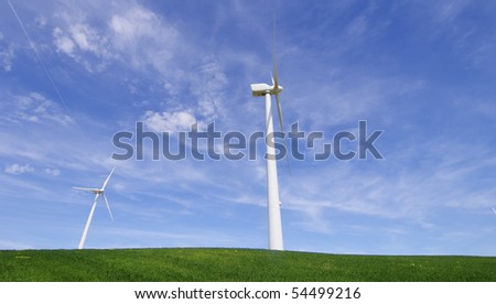 two windmills in a green meadow with blue and cloudy sky - stock photo