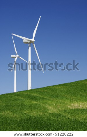 two windmills in a green meadow with blue sky - stock photo