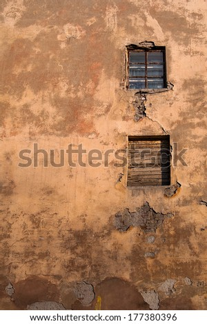 Two window on the old wall with cracked plaster. - stock photo