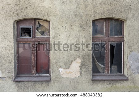 two windows completely ruined, shattered glass, shabby plaster on the wall