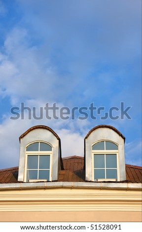 two windows in attic and blue sky at sunny day