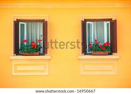 two windows on orange vivid wall with geraniums balcony - stock photo