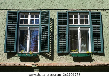 Two windows with old open shutters - stock photo