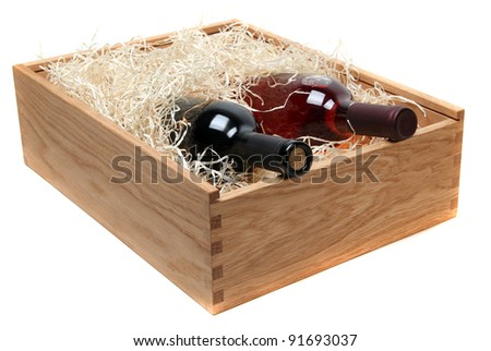 two wine bottles in wooden case with wood-wool on white - stock photo