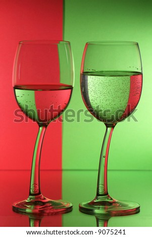 Two wine glass with red green background. - stock photo