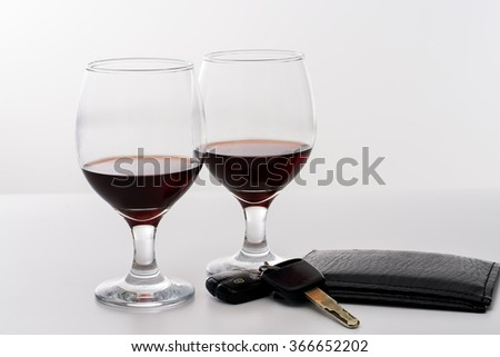 Two wine glasses beside a vehicle key and driver license, in a white background.