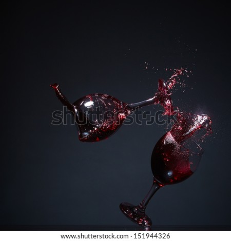 Two wine glasses falling on a table and splashing wine