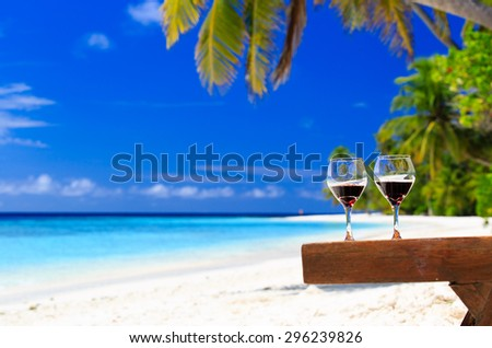 two wine glasses on sand tropical beach
