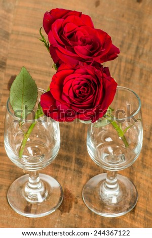 Two wine glasses with hugging roses - stock photo