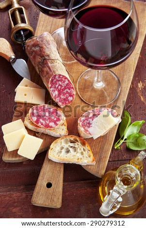 two wineglass with red wine and assortment of cheese and salami. olive oil & basil - stock photo