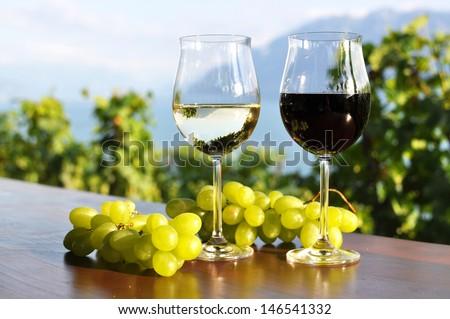 Two wineglasses and grapes against Geneva lake. Lavaux region, Switzerland - stock photo