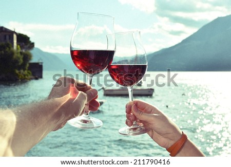 Two wineglasses in the hands against lake Como, Italy - stock photo
