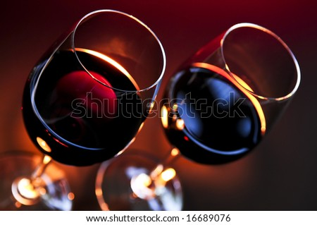 Two wineglasses with red wine at candlelight - stock photo