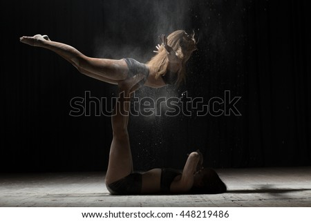 Two woman acrobatics posing and sprinkle flour on black background