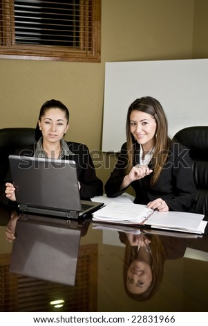 Two woman at a conference table having a meeting