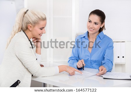 Two woman at desk - financial business meeting. - stock photo