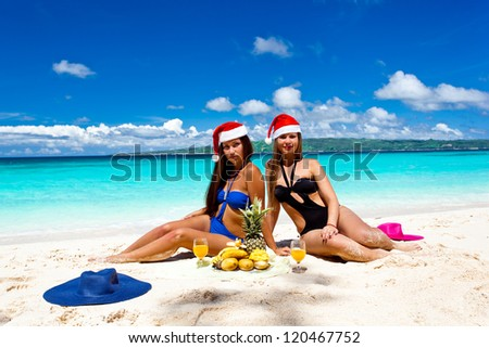 Two Woman celebrating Christmas on tropical beach