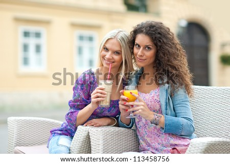 two woman friends at cafe having fun and talking