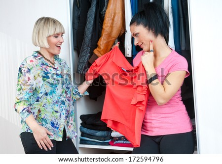 two woman friends choose clothes in front of closet - stock photo