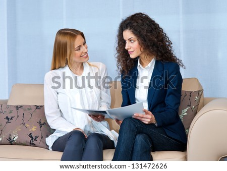 two woman friends on the sofa reading brochure or magazine