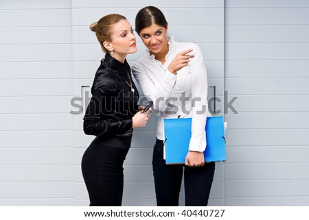 two woman gossiping in the office - stock photo
