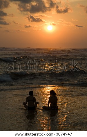 Two woman in a Lotus position as the sun sets over the pacific - stock photo