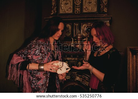 two woman in witch dress doing magic