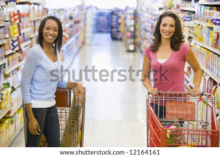Two woman meeting in supermarket grocery ailse - stock photo
