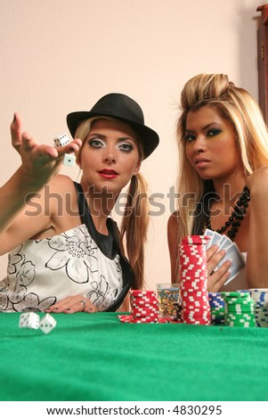 Two woman playing poker and rolling dices (action shot with dices rolling towards the camera) - stock photo