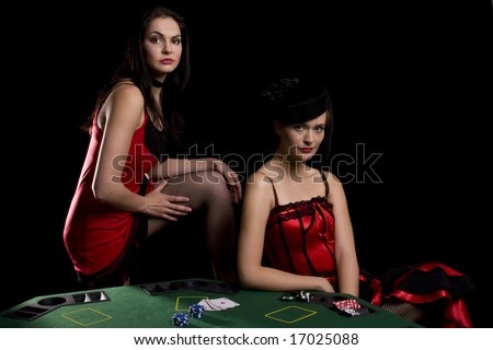 Two woman playing poker at a table with red cabaret dresses on - stock photo