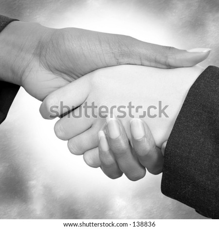 Two woman shaking hands.  Business suit sleeves.