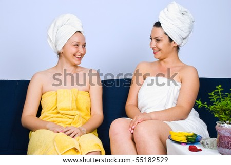 Two woman sitting on couch in a spa  salon waiting room and having a funny conversation and laughing together