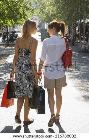Two woman walking on the street carrying shopping bags.