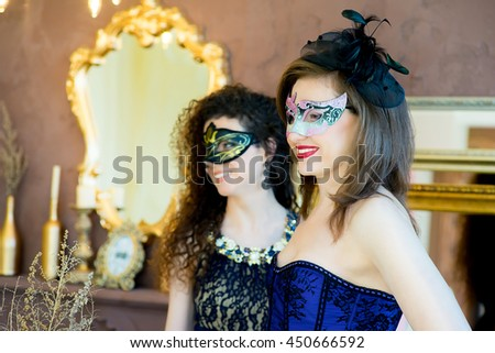 two woman with black hair and a masquerade mask posing on a brown background - stock photo