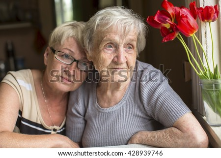 Two women, an old mother and her adult daughter sit together near the window. - stock photo