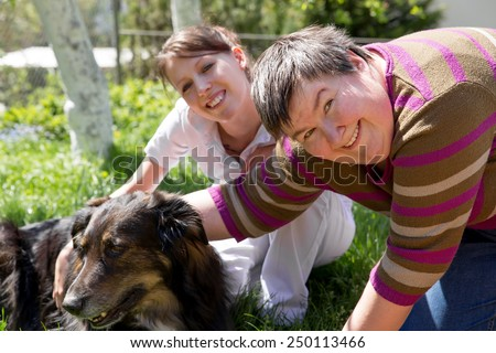 two women and a half breed dog on a field - stock photo