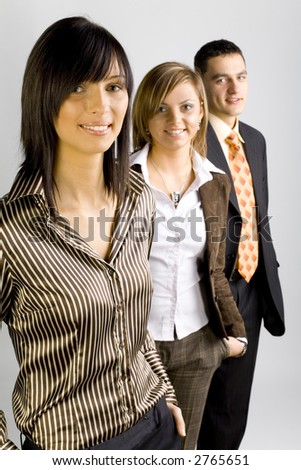 Two women and a man are standing, looking at the camera and smiling. Focus is on the first person. - stock photo