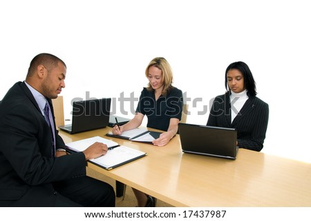 Two women and a man sit at conference table at a business meeting - stock photo