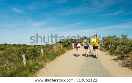 Two women and a man walking with bags through the dunes to the beach on a sunny day in the summer season.