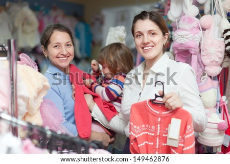 Two women and child chooses wear at clothes store. Focus on woman - stock photo